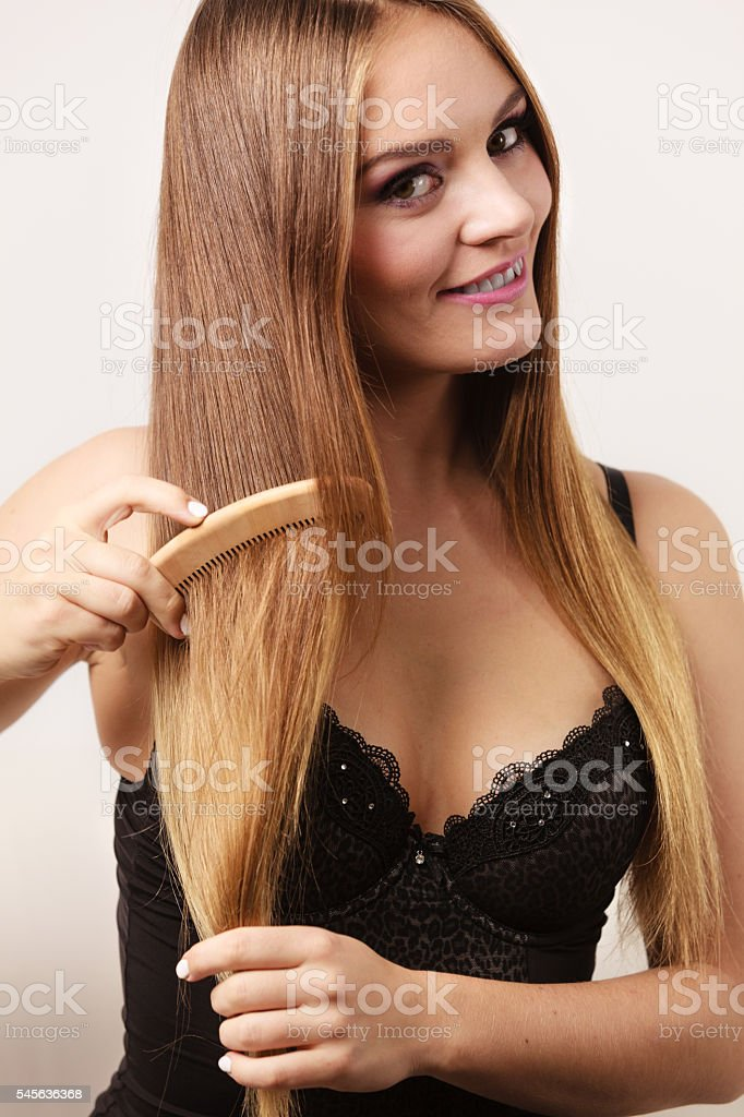 Woman combing her long hair with wooden comb stock photo
