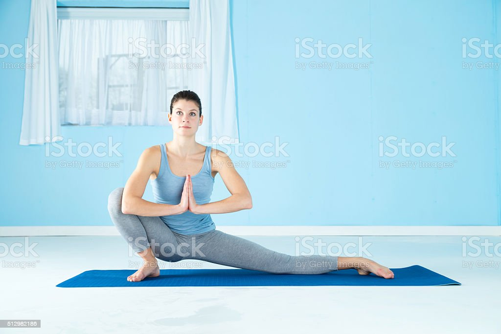 Woman Combining Yoga And Gymnastics stock photo