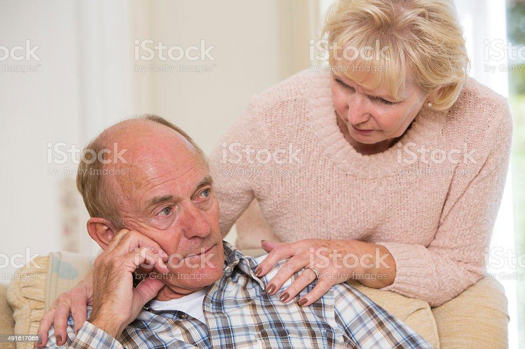 Woman Comforting Senior Man With Depression stock photo