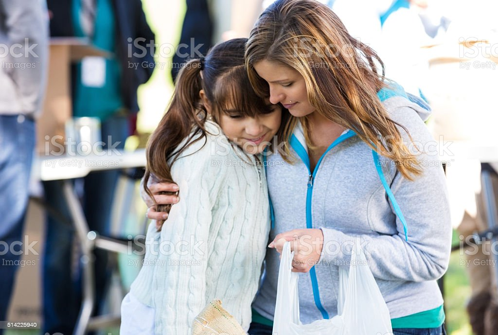 Woman comforts daughter at clothing drive stock photo