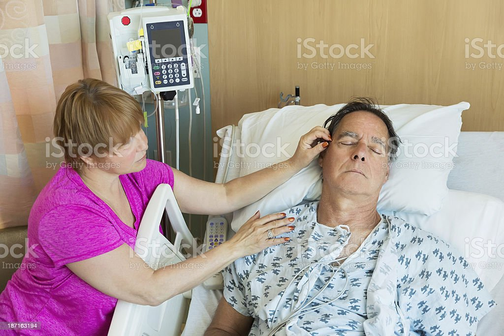 Woman comforts sick mature man in hospital royalty-free stock photo