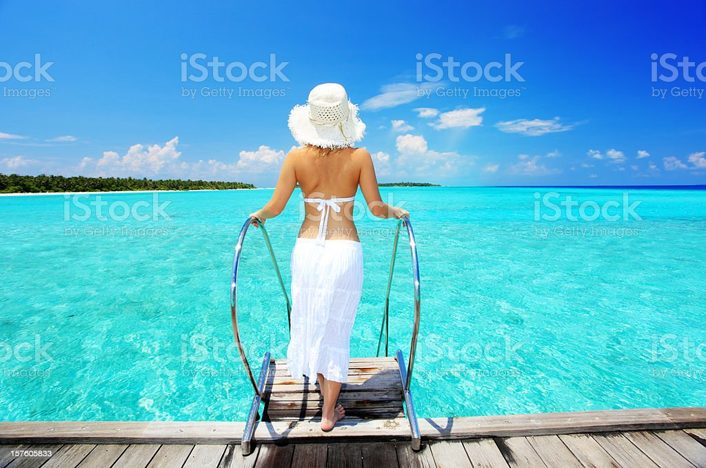 Woman coming down stairs entering the transparent sea on Maldive stock photo
