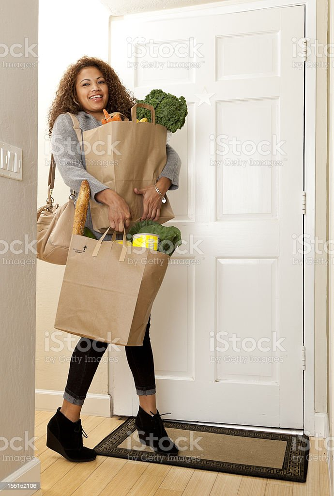woman coming home with grocery bags stock photo