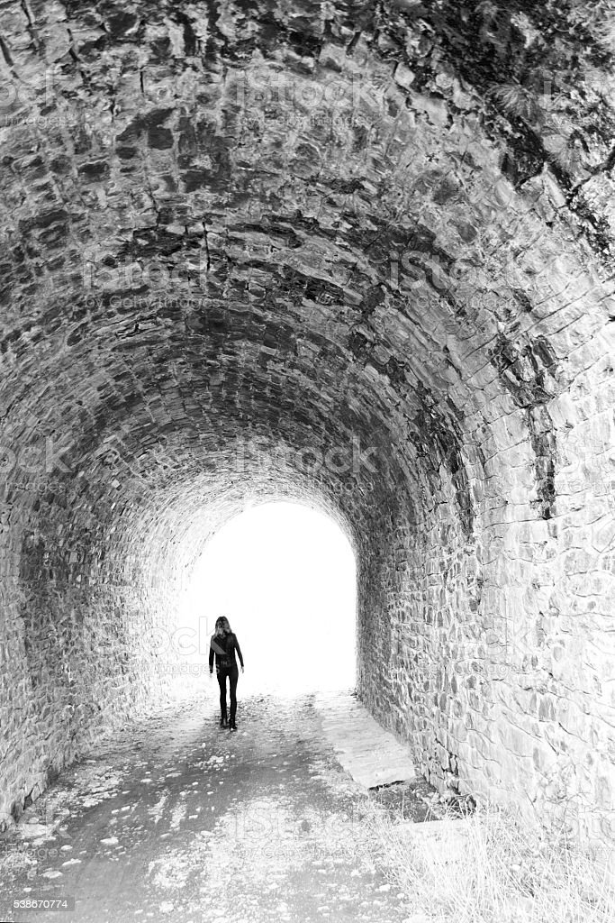 Woman coming out of the tunnel stock photo