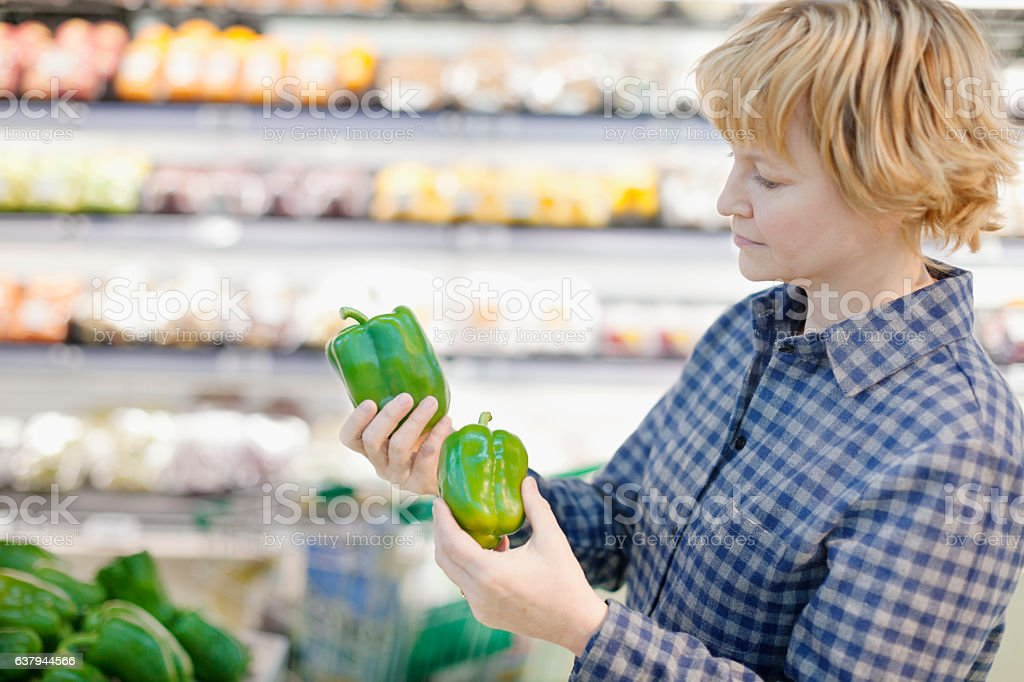 Woman comparing green bell peppers in grocery store produce aisle stock photo