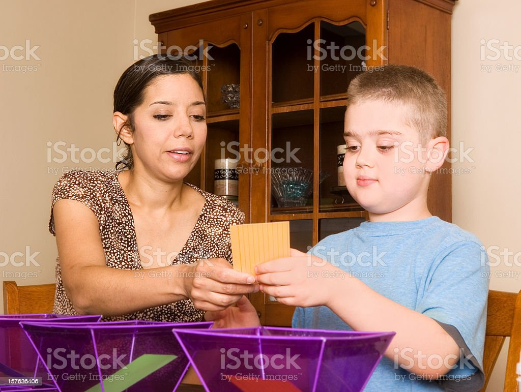Woman conducting ABA therapy with special needs child stock photo