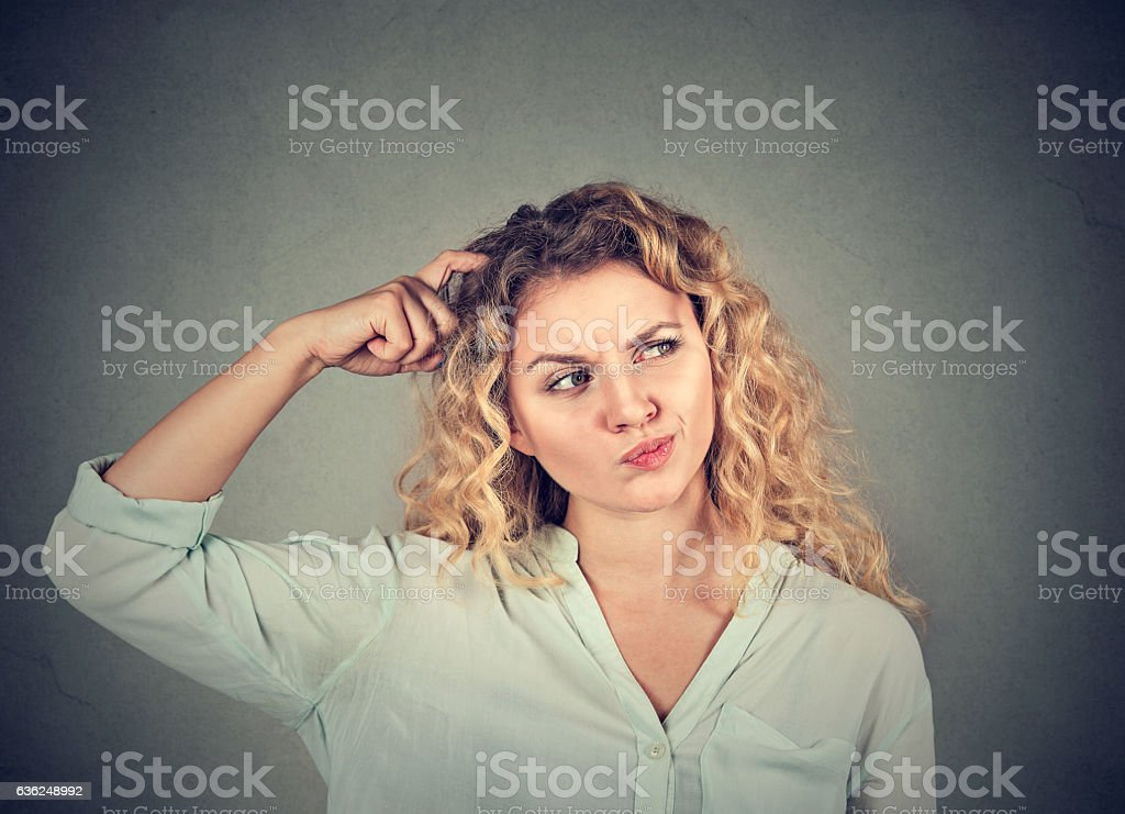 Woman confused scratching head thinking looking up stock photo