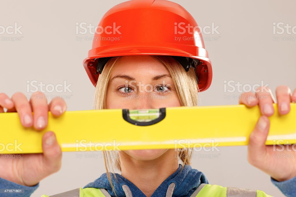 Woman construction worker checking the spirit level royalty-free stock photo