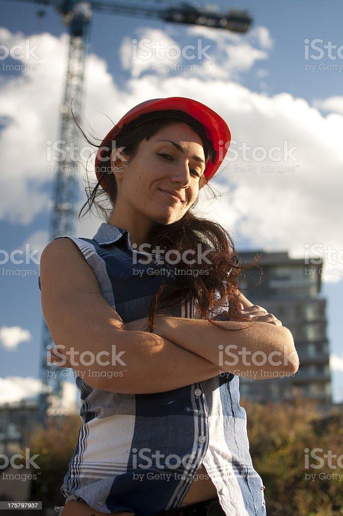 Woman construction worker wearing orange safety helmet royalty-free stock photo