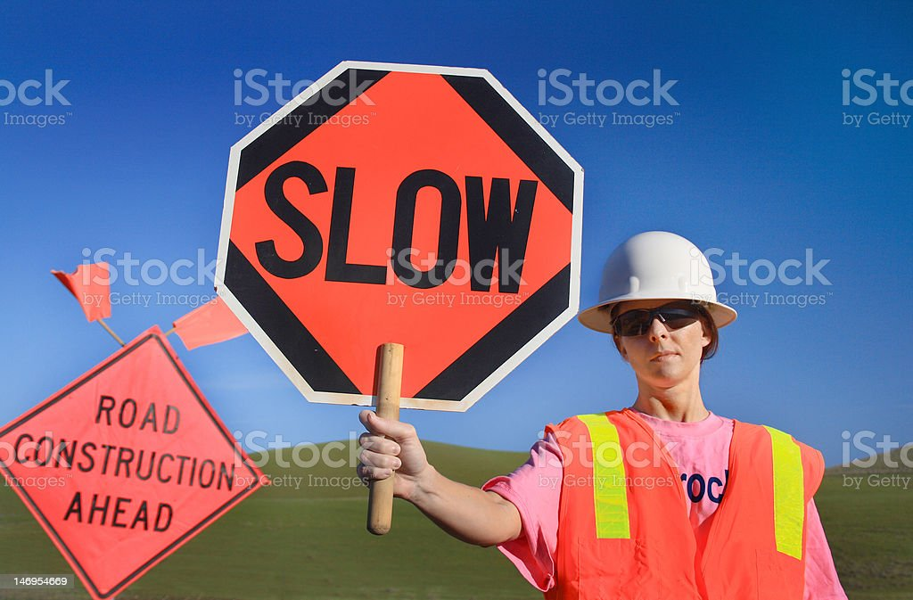 Woman Construction Worker with Slow Sign stock photo