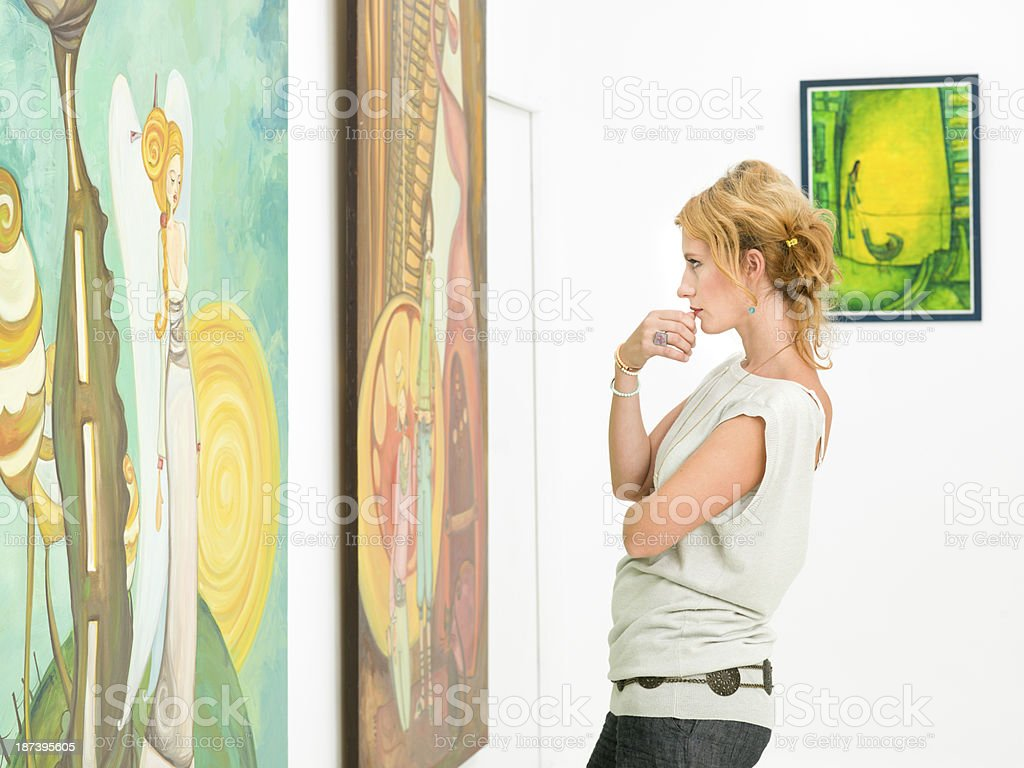 woman contemplaing colorful paintings stock photo