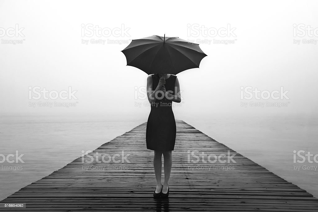 woman contemplates peacefully in front of a mysterious lake stock photo