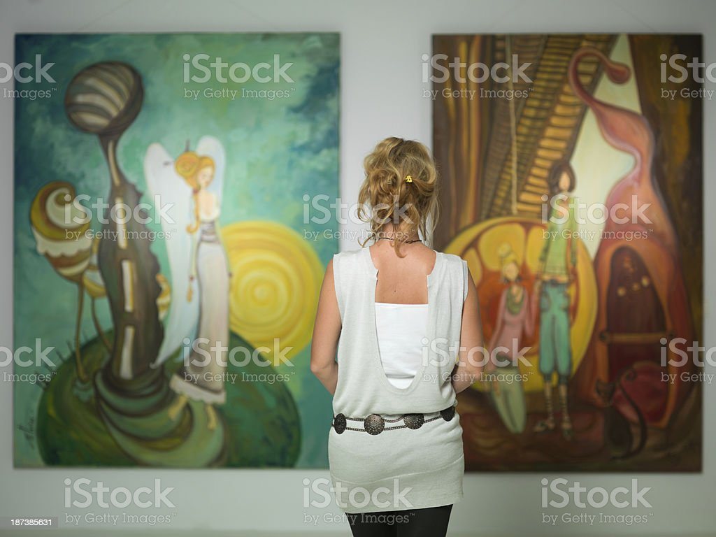 woman contemplating colorful paintings stock photo