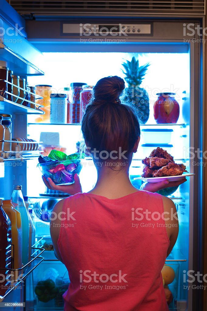 Woman Contemplating Healthy and Unhealthy Eating Choices stock photo