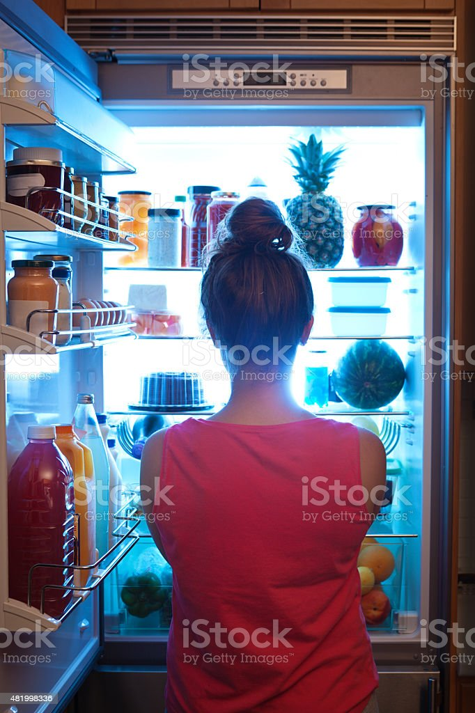 Woman Contemplating Midnight Snack late Night with Open Refrigerator stock photo