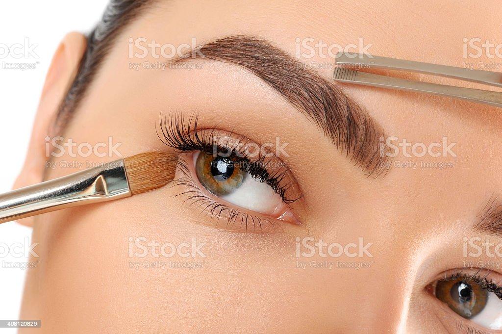 Woman contouring eyebrows and applying eye make up stock photo