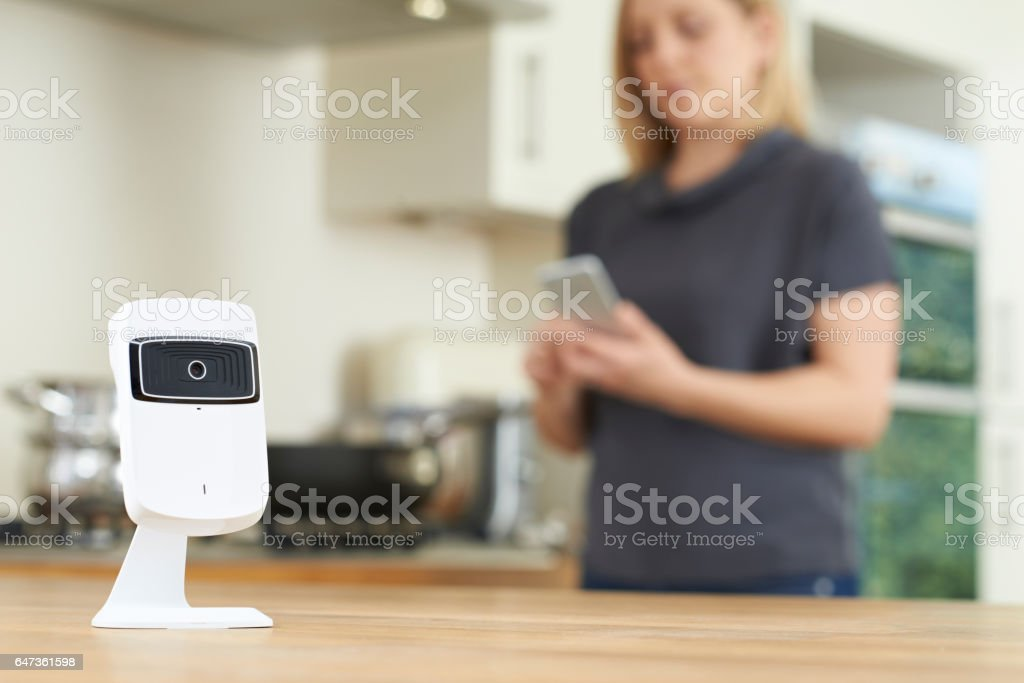 Woman Controlling Smart Security Camera Using App On Mobile Phone stock photo