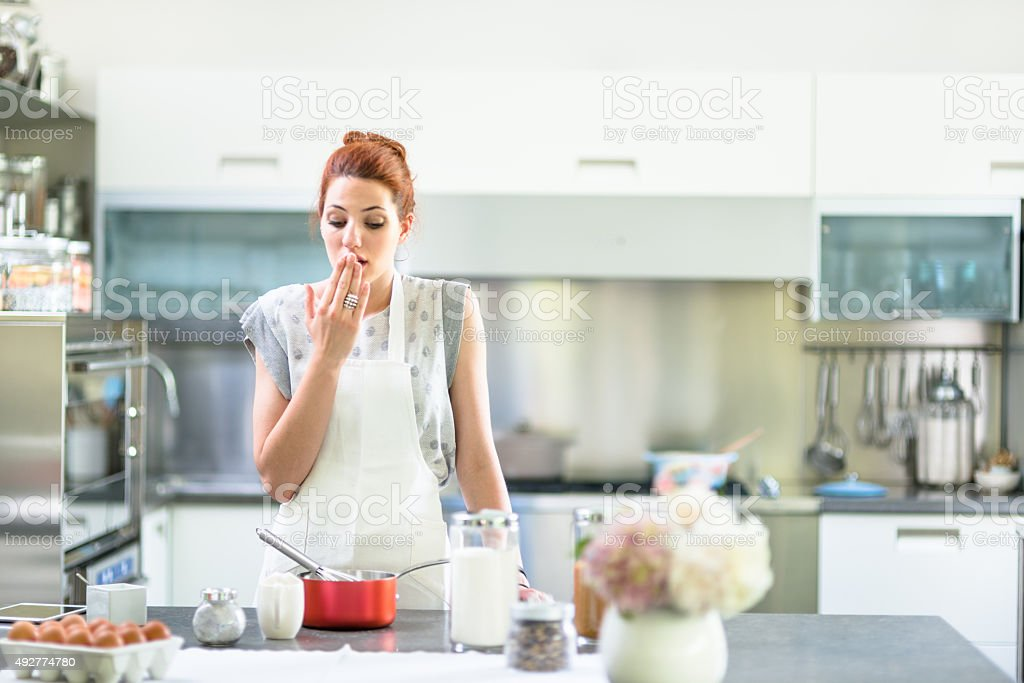 Woman cooking a cake on the kitchen stock photo