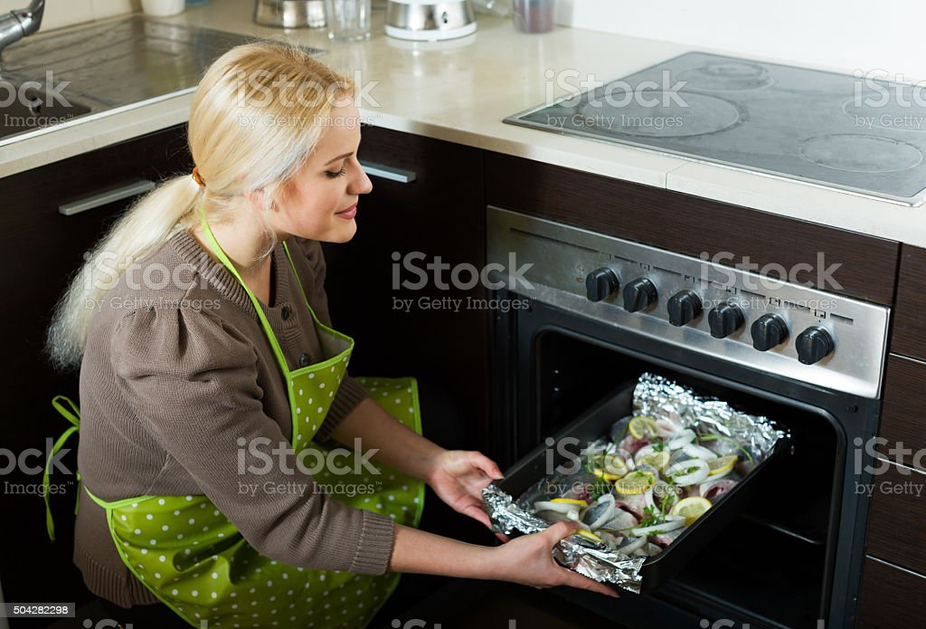 Woman cooking fish  in oven stock photo