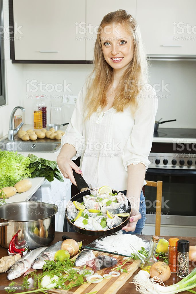 woman cooking fish with lemon in frying pan stock photo