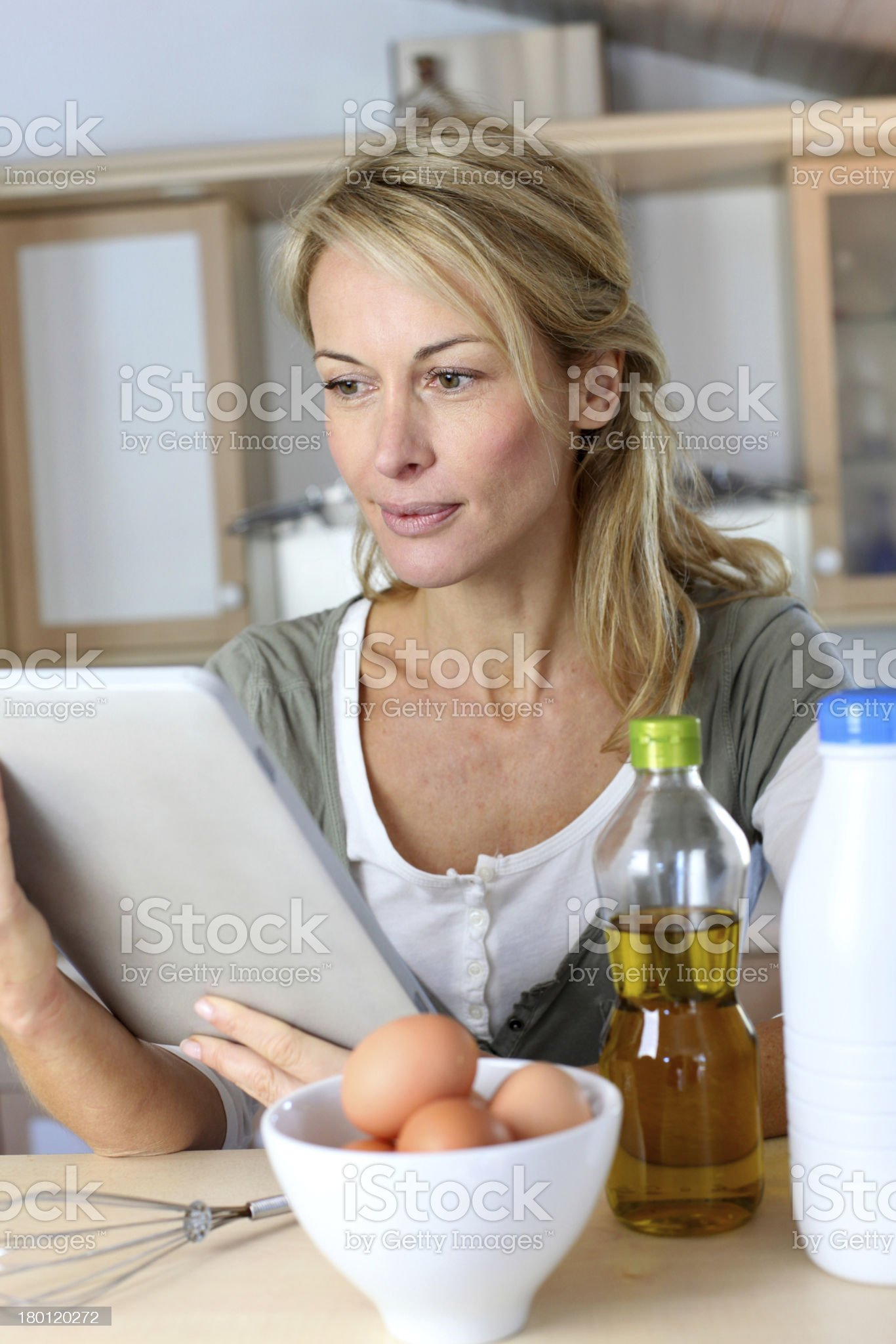 Woman cooking in kitchen with help of internet royalty-free stock photo