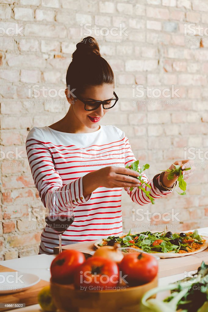 Woman cooking in the modern kitchen, preparing pizza stock photo