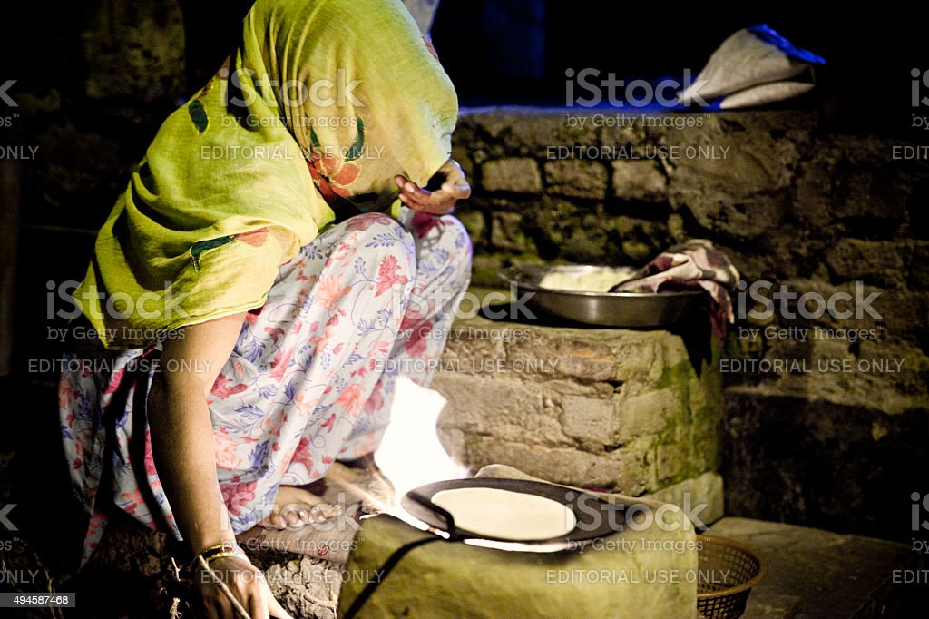 Woman cooking in the street in evening stock photo
