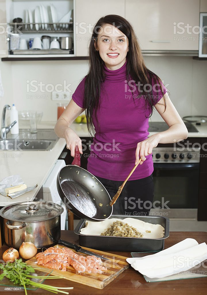 woman cooking pie with salmon stock photo