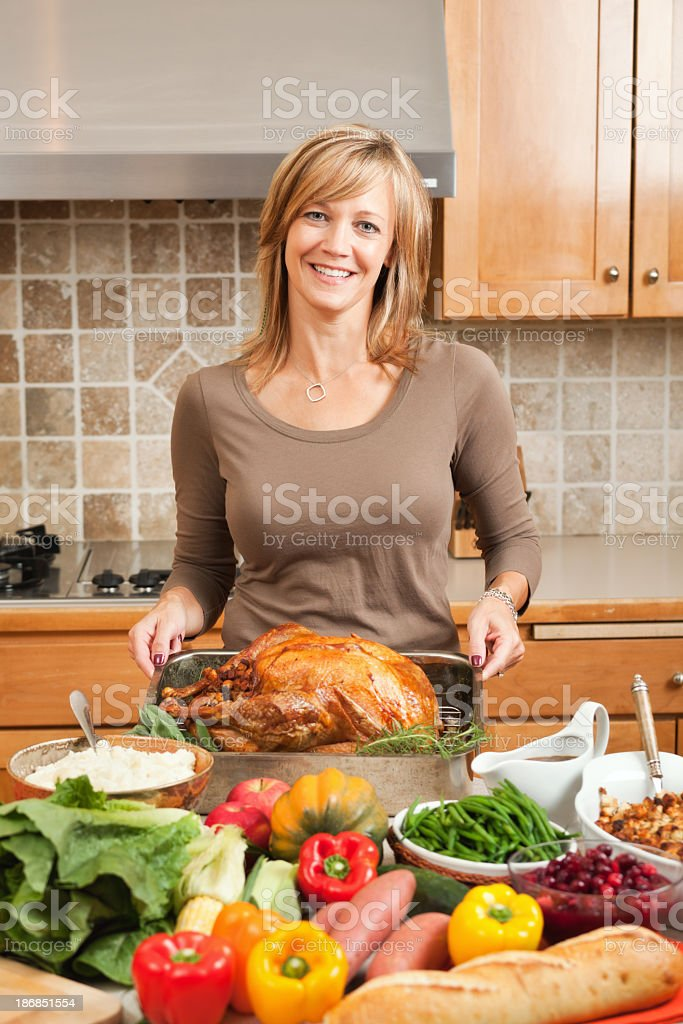 Woman Cooking Thankgiving Turkey Holiday Dinner in Kitchen, Displaying Meal stock photo