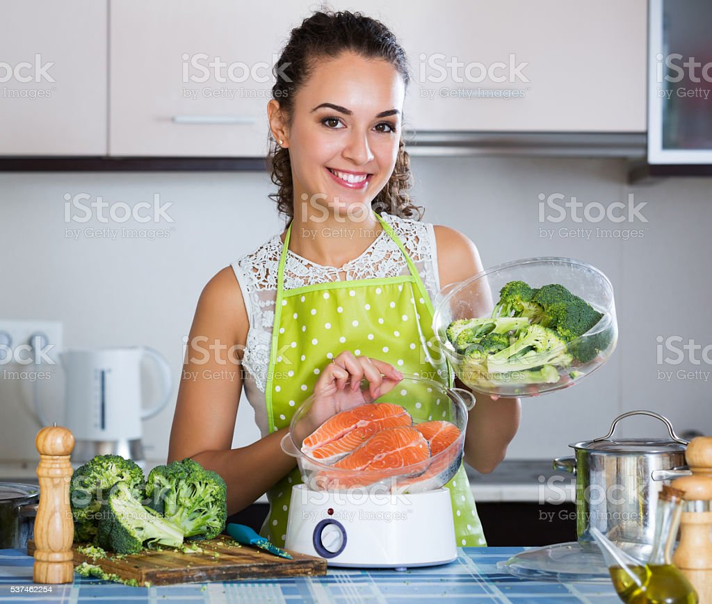 Woman cooking trout in steamer stock photo
