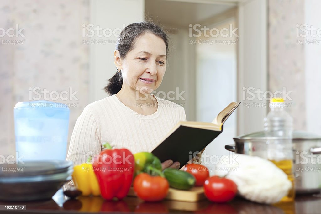 woman cooking with cookbook in kitchen at home royalty-free stock photo
