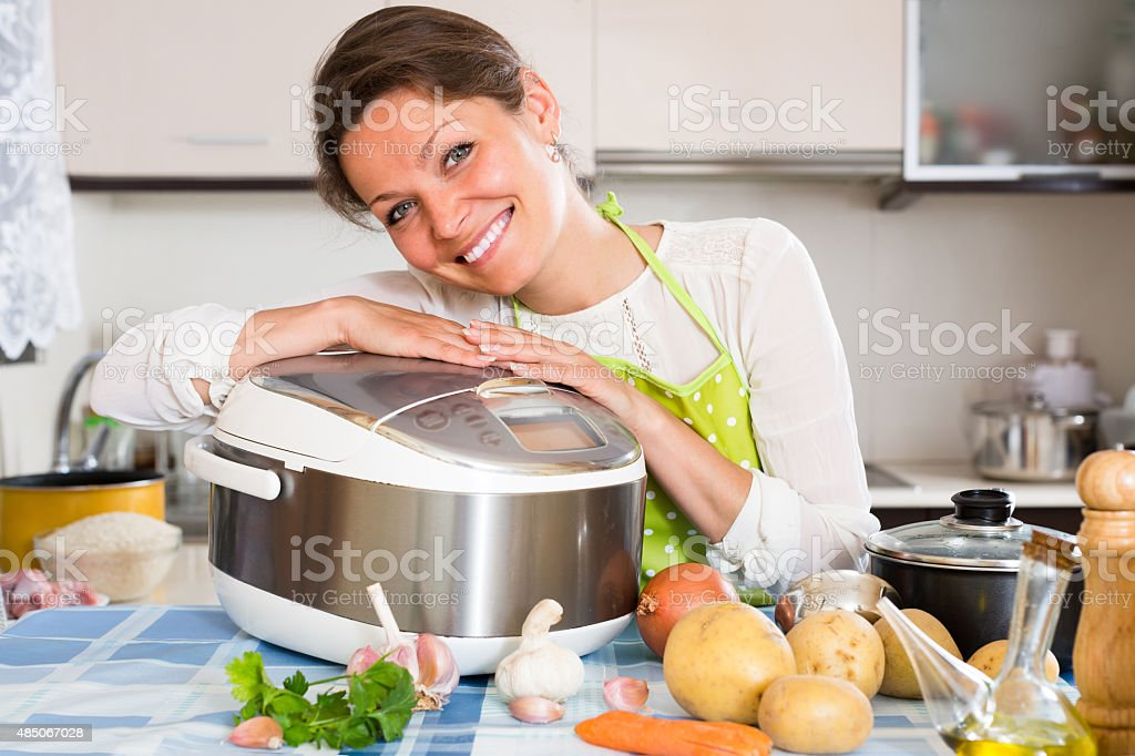 Woman cooking with multicooker stock photo