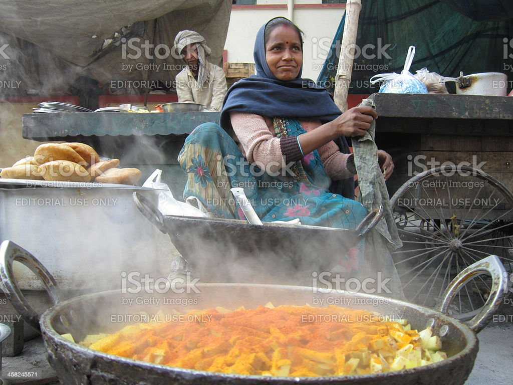 Woman cooks colorful food at street side stall. stock photo