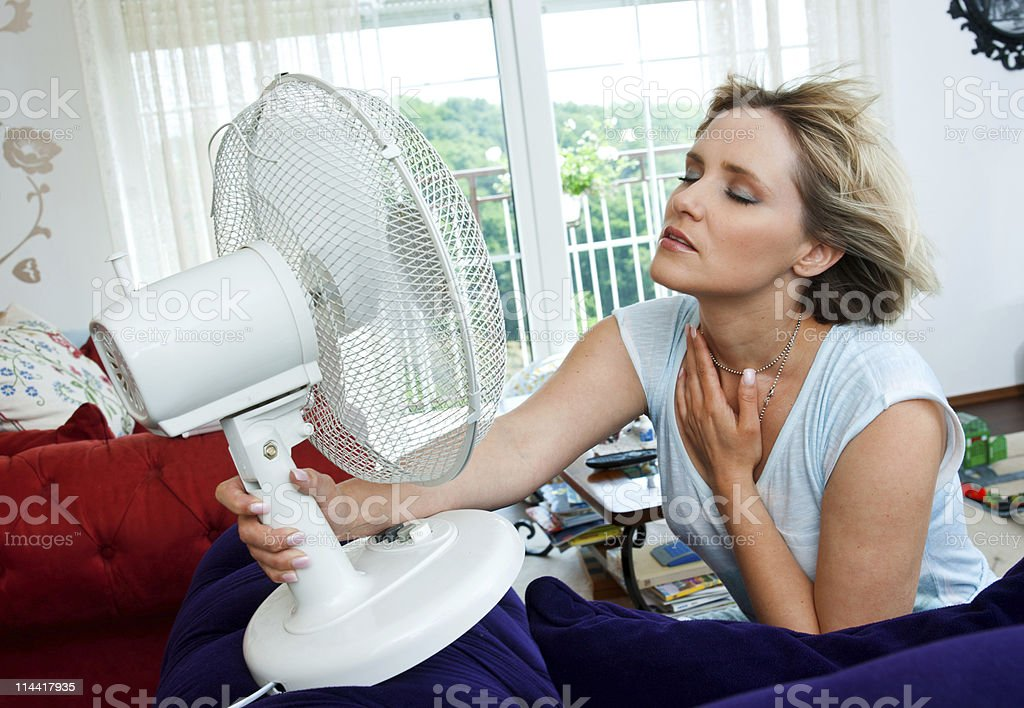 woman cooling herself stock photo