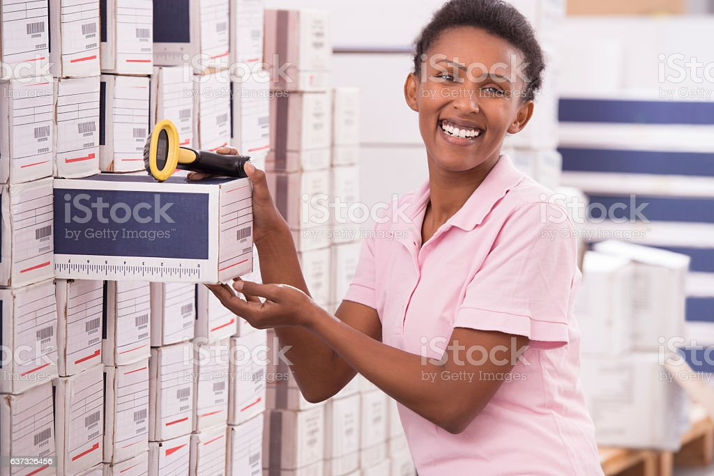 Woman counting goods in warehouse. stock photo