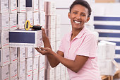 Woman counting goods in warehouse.