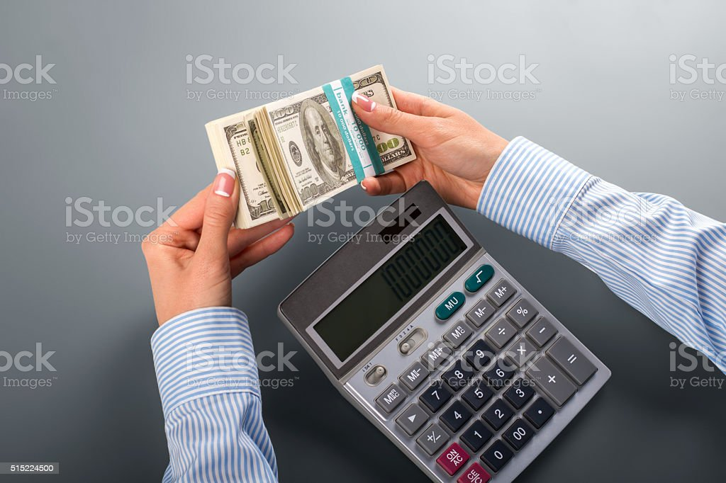 Woman counting money with calculator. stock photo