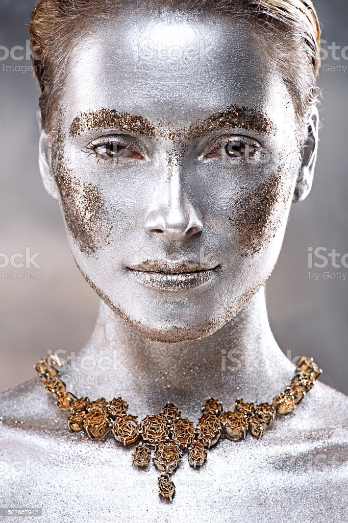woman covered by sliver paint wearing luxury jewellery stock photo