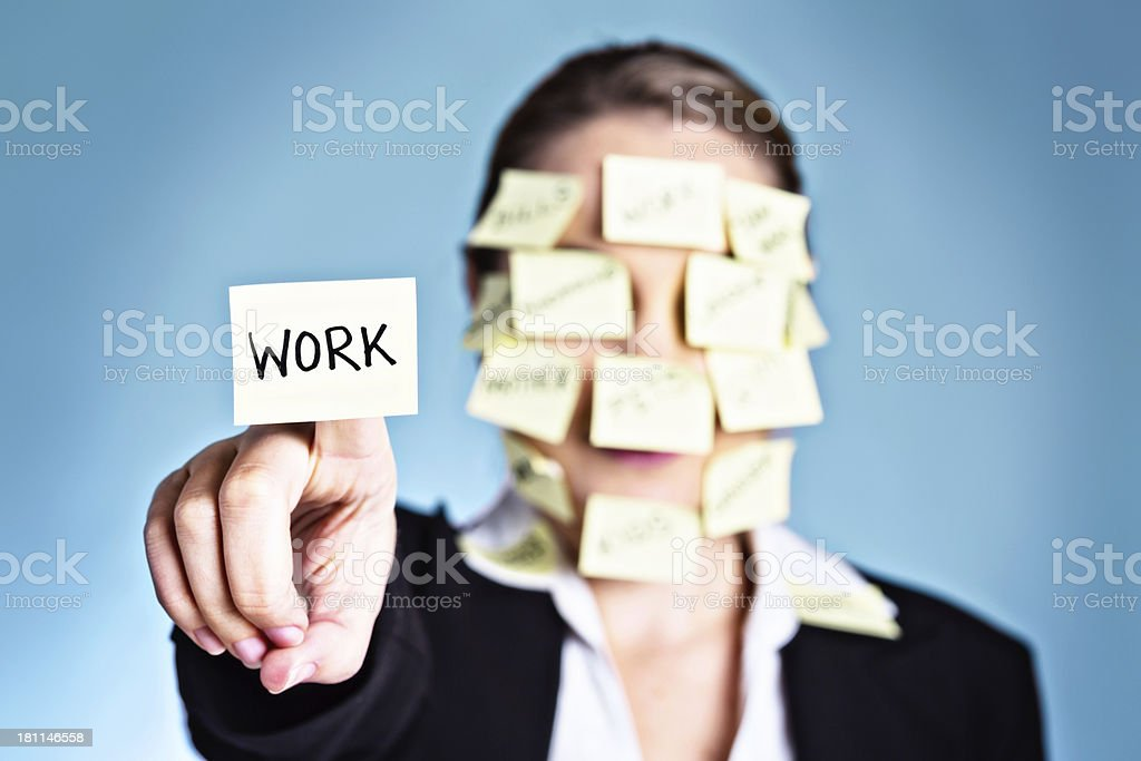 Woman covered in sticky reminders holds one labeled simply WORK royalty-free stock photo