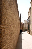 Woman covered with hijab walking in alley