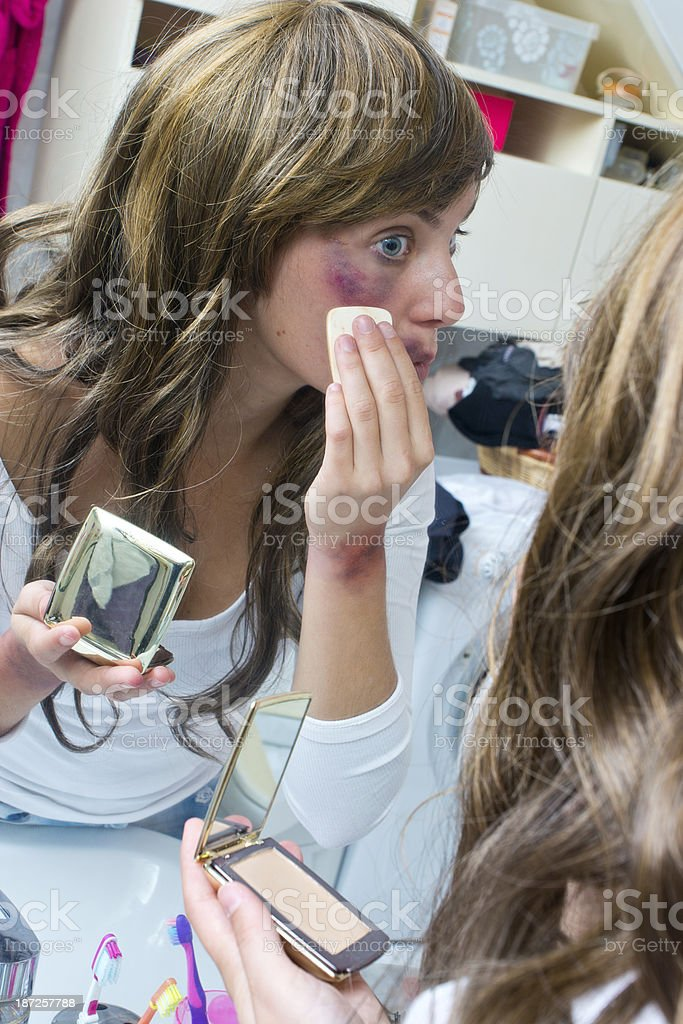 Woman covering bruises on her face with make-up stock photo