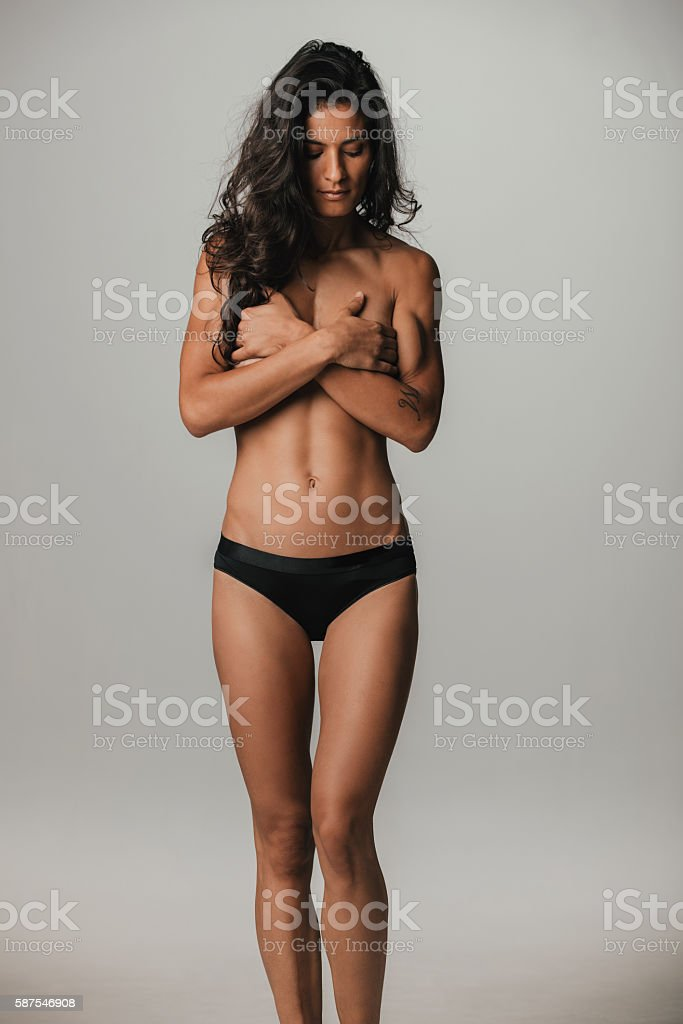 Woman covering chest over gray background stock photo