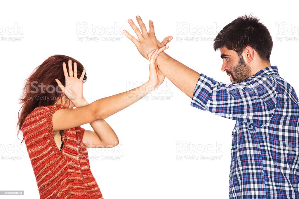 Woman covering face from violent husband stock photo
