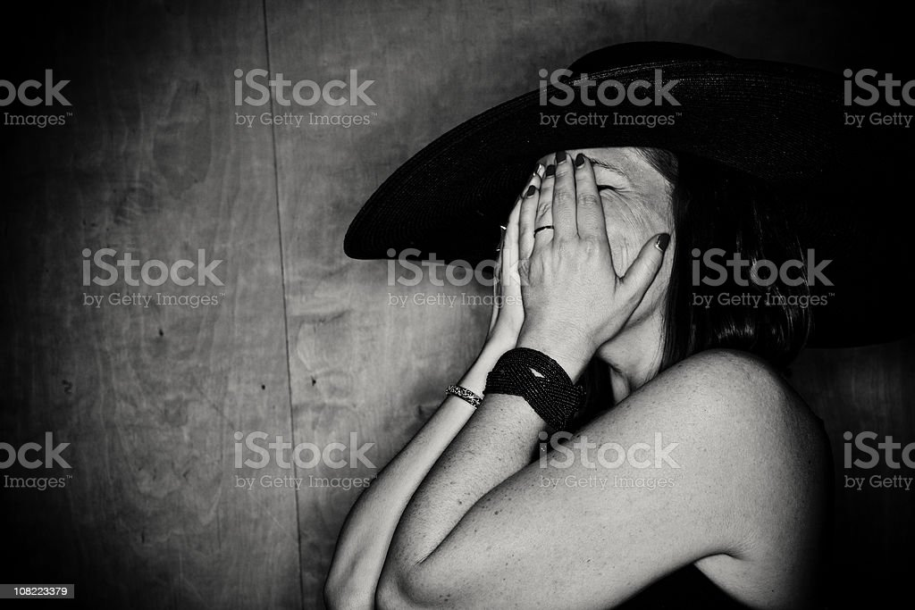 Woman Covering Face with Hands Wearing Hat, Black and White royalty-free stock photo