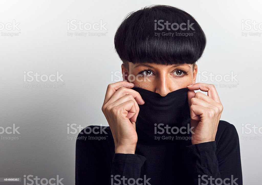 Woman covering face with turtleneck looking at the camera stock photo