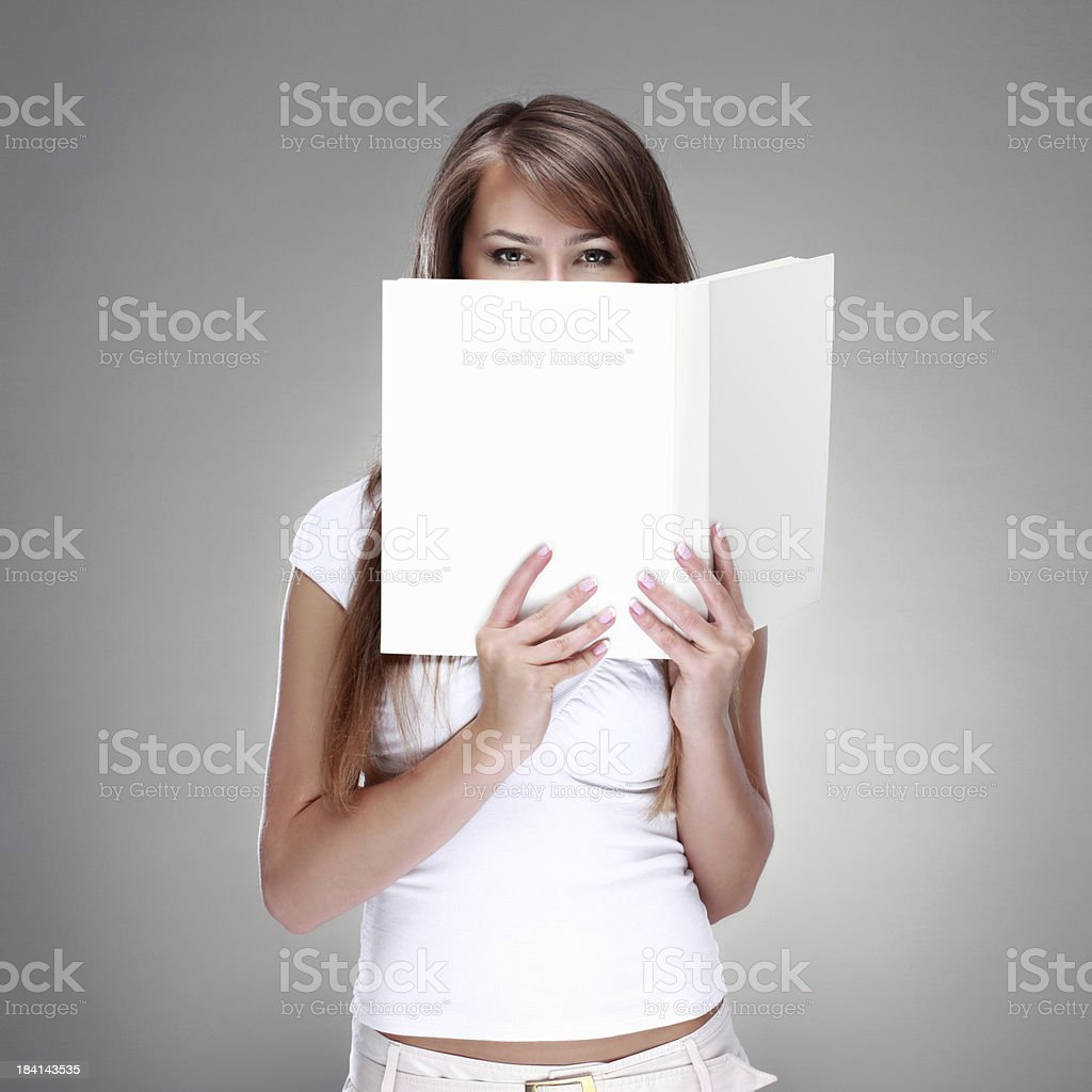 Woman covering face with white book royalty-free stock photo