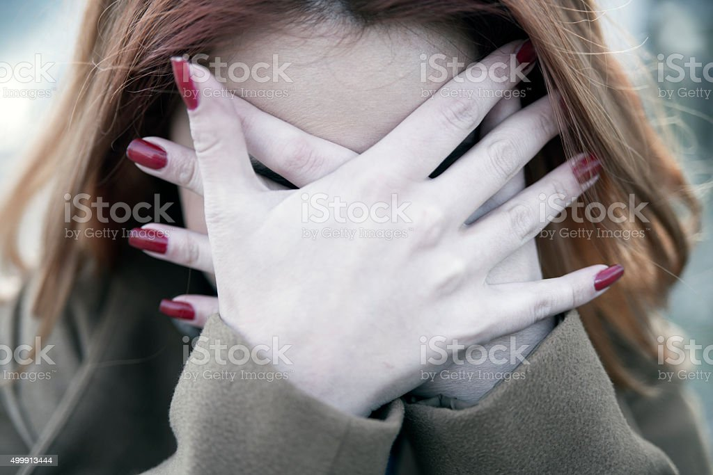 Woman covering her eyes-Scared woman stock photo