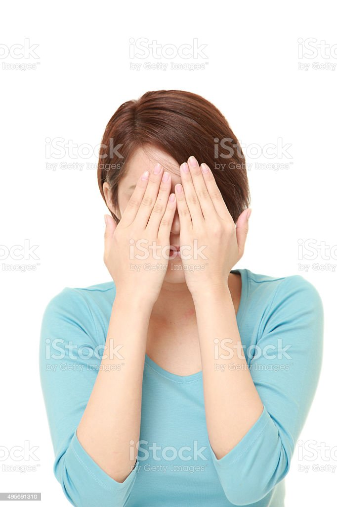 woman covering her face with hands stock photo
