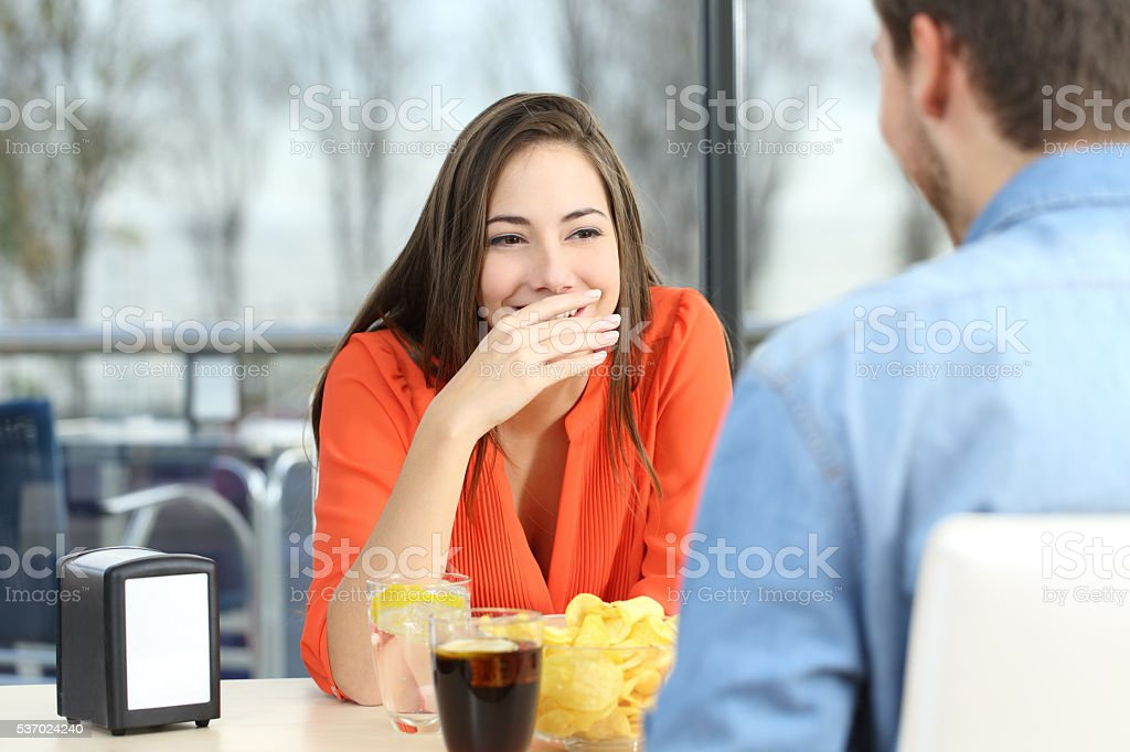 Woman covering her mouth to hide smile or breath stock photo
