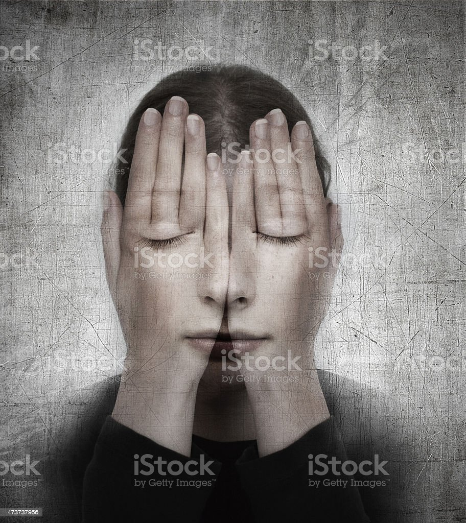 Woman covers her face with hands on the grunge backround. stock photo